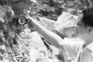 ■地质专家拿着地质罗盘测量。