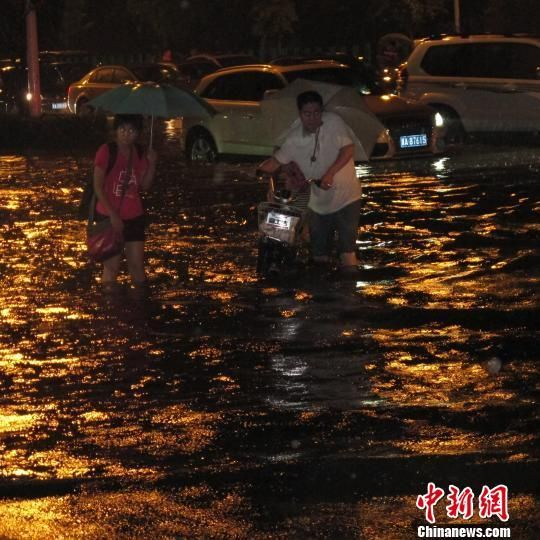 行人在水中艰难前行。
