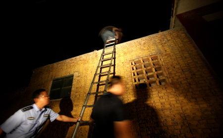 ■3日凌晨1时50分许,解救小组成员小心翼翼地翻墙入院,准备解救一名被拐卖的男婴