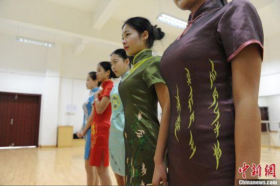 """11月15日,5名湖南女子学院的学生身着""""女书""""旗袍在校园里亮相。据这5套旗袍的设计者介绍,女书""""旗袍分为红、黄、青、蓝、紫五件不同颜色,旗袍上有大小不一的""""女书""""。"""