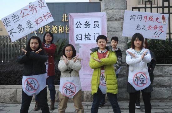 """11月26日上午11时许,武汉,在湖北省劳动厅门口,大学生们表演""""公务员考试男女平等,不做妇检""""的行为艺术,抗议女大学生参加公务员考试体检被要求妇检。"""