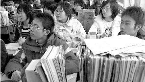 某中学,学生们的课桌上摆满了课本和习题本。