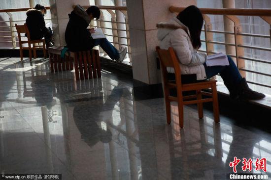 """济南,在山东建筑大学,狭窄的过道上摆满了一排排自习课桌,坐满了备战考研的考生。随着全国研究生考试的临近,大学校园""""一座难求""""的现象又开始上演。"""