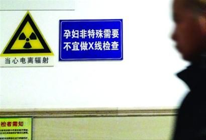 """□医院的X光室门口,贴有""""当心电离辐射""""的告示。"""