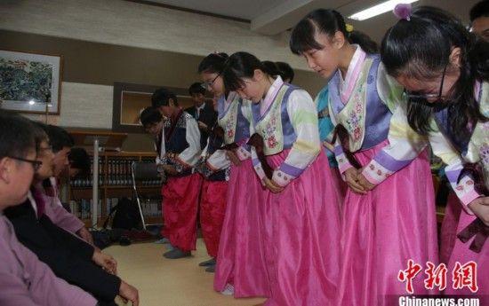 当地时间2013年2月15日,韩国釜山,小学生们身穿韩服参加毕业典礼。