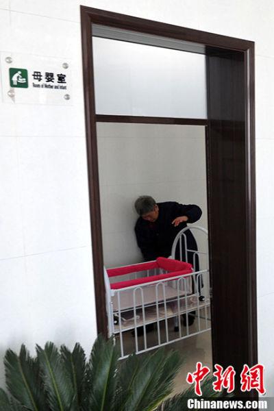 3月5日,在一公厕内,管理人员在母婴室内检查婴儿床。