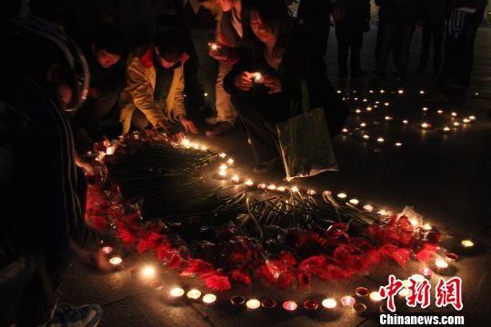 络绎的市民纷纷献上鲜花,在烛光下共同为四川雅安地震受灾的同胞祈福。 陈昊 摄