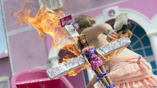 被绑在十字架上烧毁的芭比娃娃