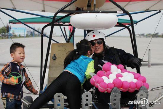 第一个架次的飞行稳稳地落地,薛有勤的孙子、孙女跑到爷爷跟前给爷爷献上气球和吻。记者 魏永贤 摄
