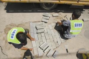 ■抢修工人午饭时间仍忙着施工。