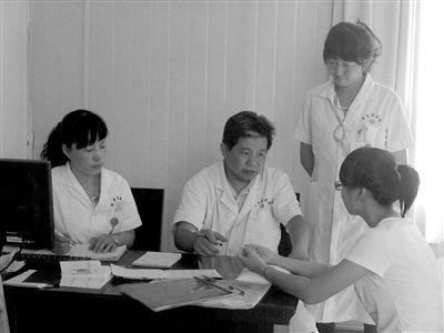 徐文江(左)正在为病人看病。 本报记者 孟洁 摄
